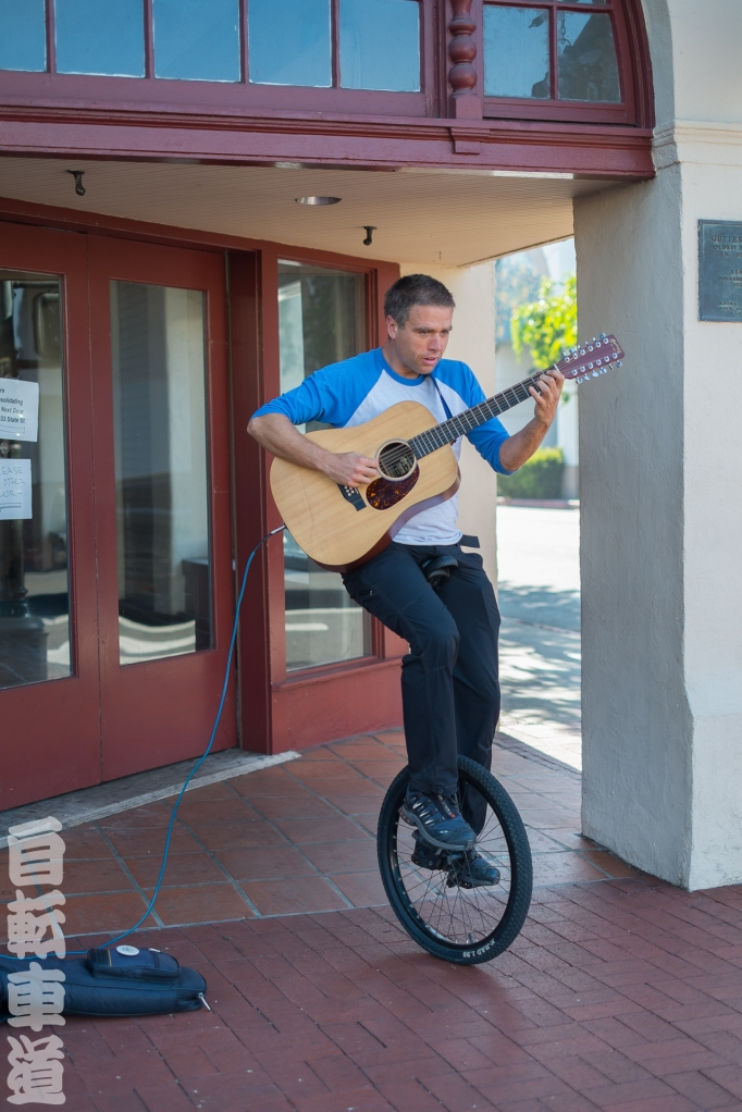 Uni-fred riding a unicycle playing a guitar. Shot on State Street in Santa Barbara, CA.